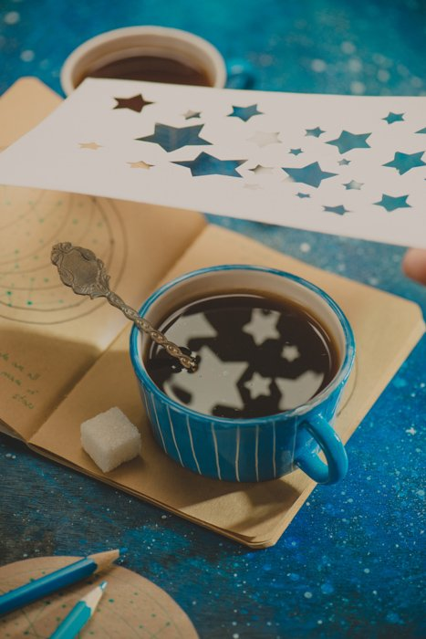 a creative still life featuring star shaped reflections in a coffee cup