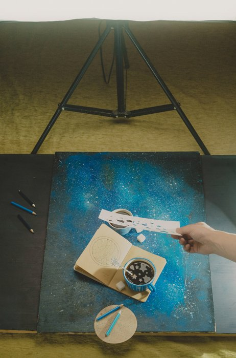 a creative still life setup featuring star shaped reflections in a coffee cup