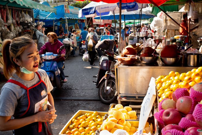 studio portrait of a female vendor in a busy market shot using fill light sources