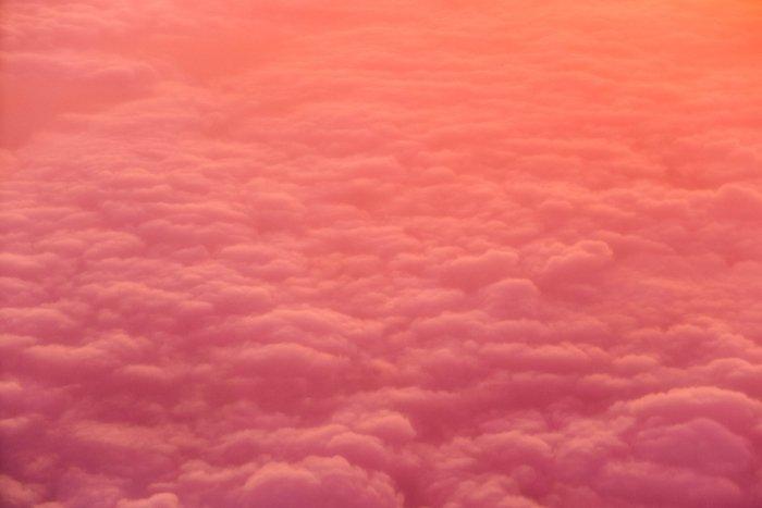 从上方拍摄的一张粉红色和橙色的多云天空照片