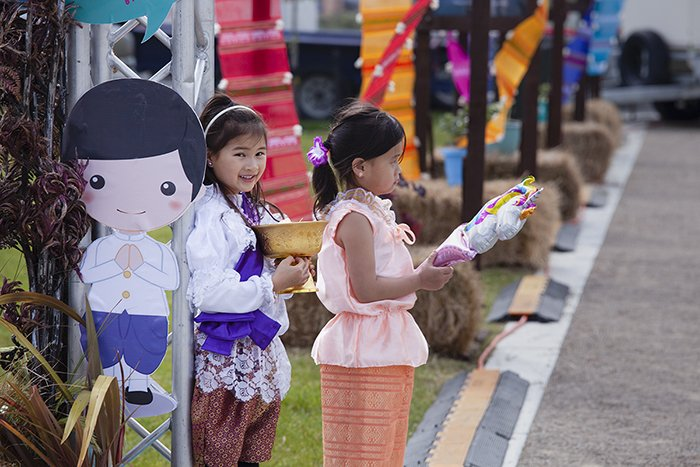 candid street photo of two little girls holding festival objects