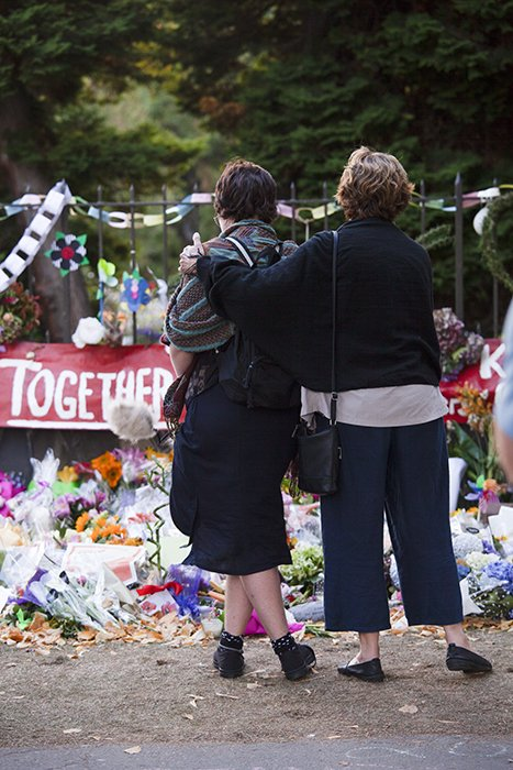candid street photo of two women comforting each other by a memorial
