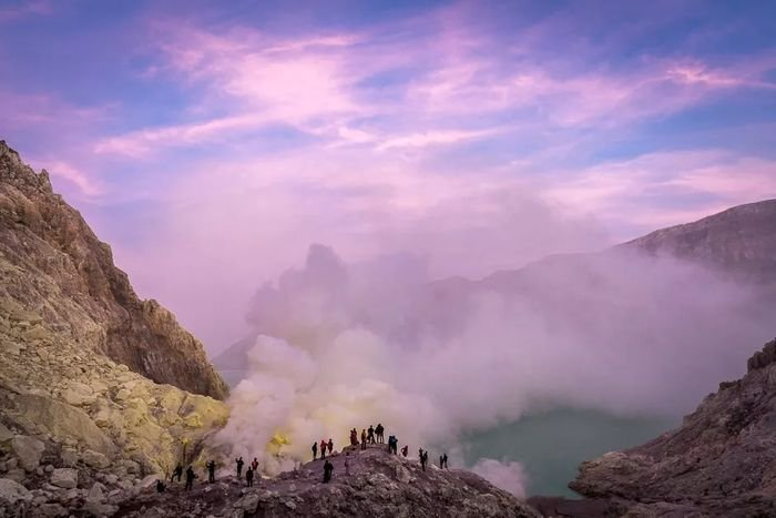 Photo of people standing on a cliff with the beautiful purple sky above