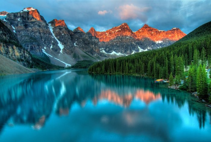 a dramatic photo of a lake surrounded by a mountainous landscape, utilizing dynamic range in photography