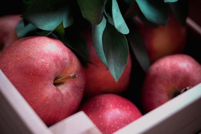 red apples in a box - symbolism in photography