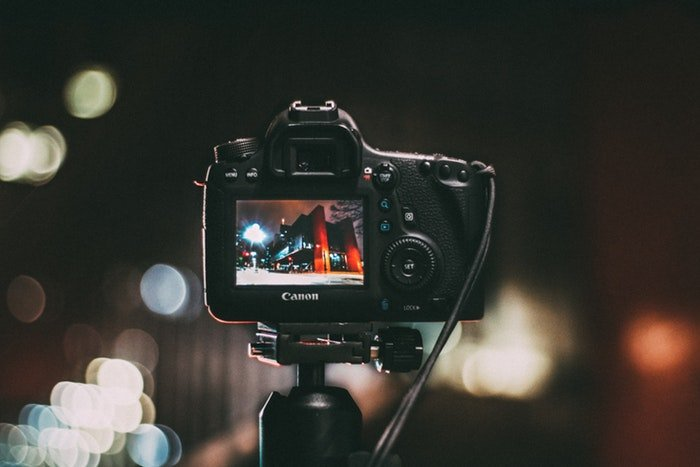 A DSLR on a tripod outdoors at night
