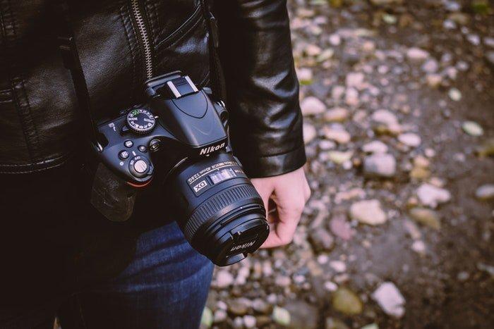 a close up of a photographer carrying a Nikon DSLR