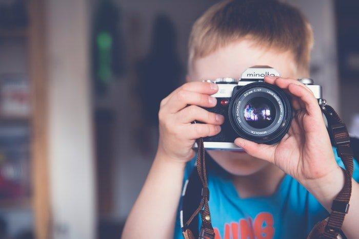 a little boy taking photos with a minolta camera