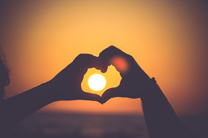 the silhouette of a persons hands making a love heart shape around a setting sun