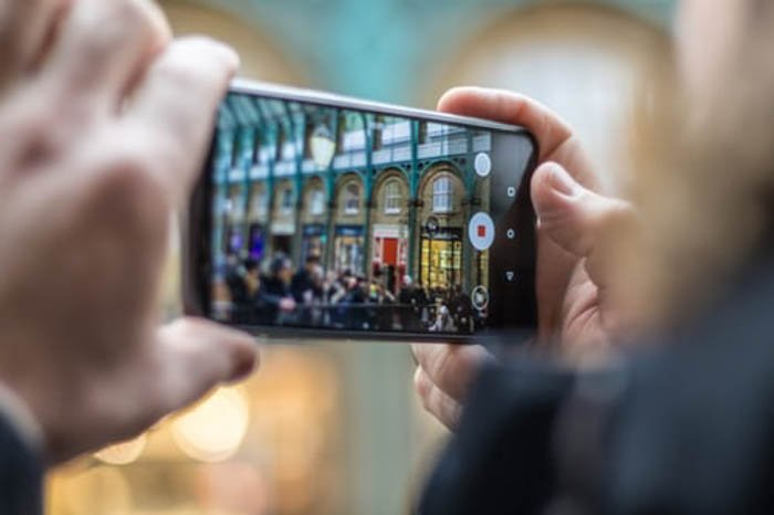 a person shooting a street photo with a smartphone- iphone vs android camera