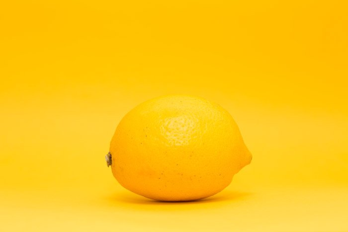 a lemon on yellow background - symbolism in photography