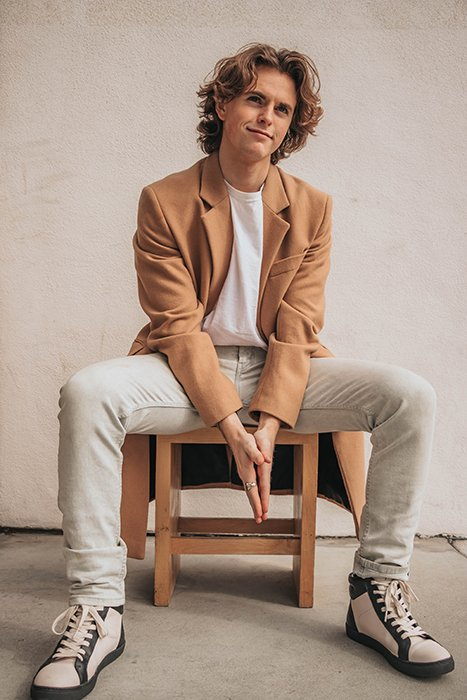 a minimalist portrait of a male model posed on a wooden chair indoors