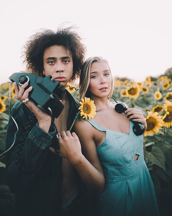 a minimalist portrait of a couple holding an old fashioned telephone in a sunflower field