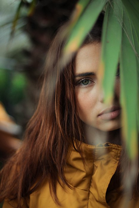 a minimalist portrait of a female model with green leaves in the foreground