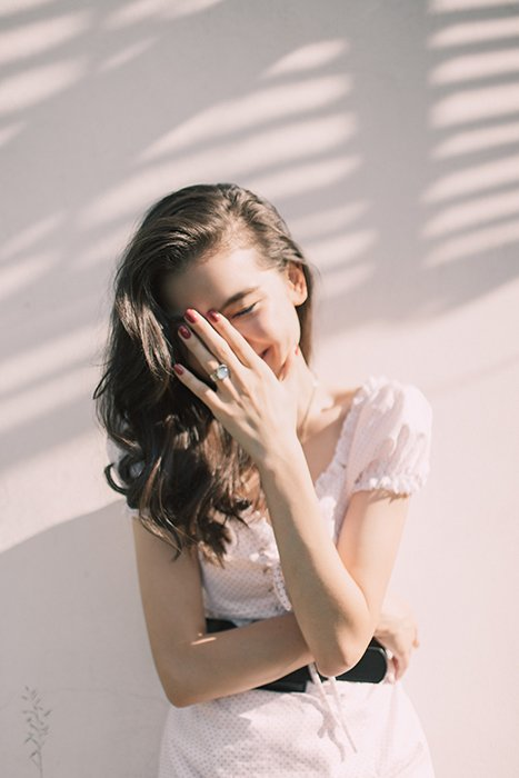 a minimalist portrait of a female model covering her laughing face with her hand