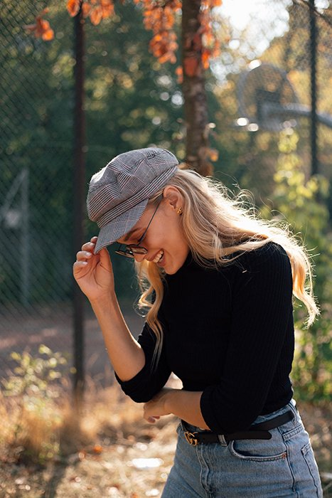 a minimalist portrait of a female model laughing outdoors
