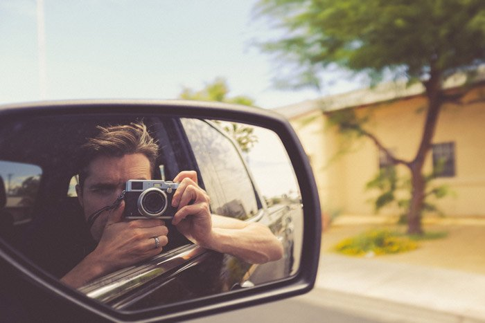 the reflection of a photographer in a car side mirror - symbolism in photography