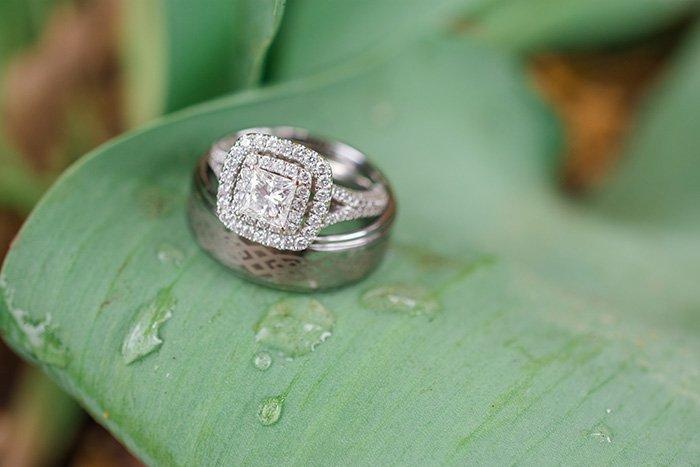 wedding rings resting on a rain covered leaf