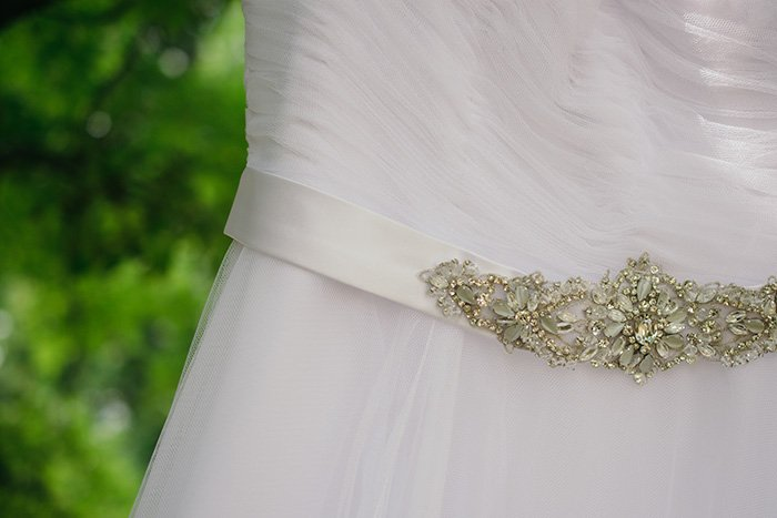a close up of details of a wedding dress at an outdoor wedding photography shoot
