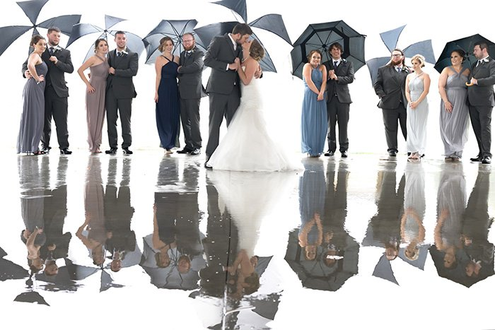a group wedding shot of the bridal party holding umbrellas in the rain