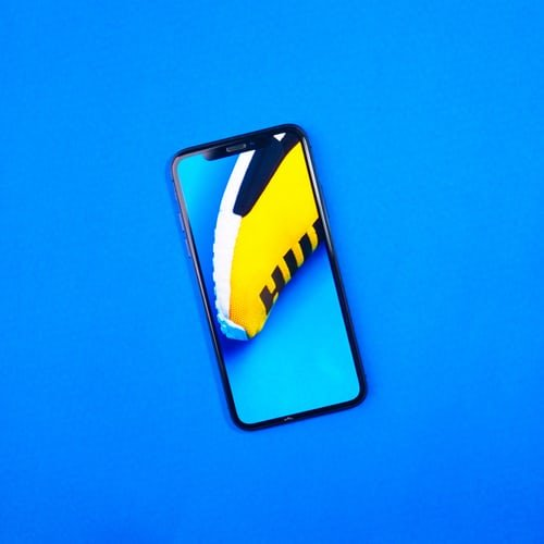 a product shot of a smartphone on blue background - iphone vs android camera