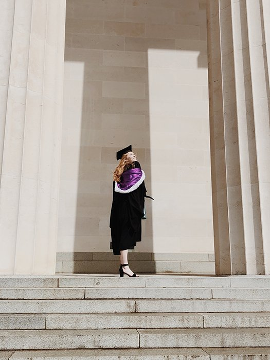 a graduate from a photography school standing outside the university