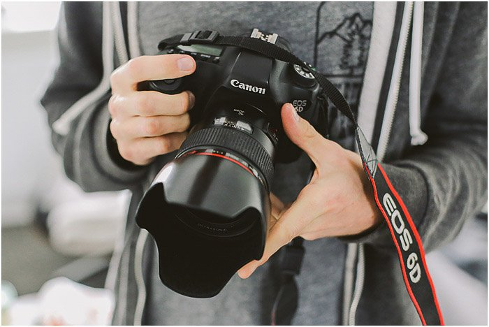 a professional portrait photographer holding a canon DSLR - portrait photography pricing