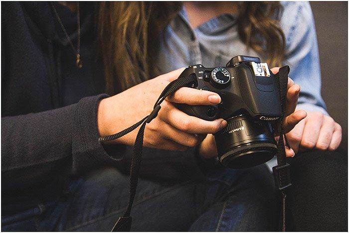 potrrait photographer reviewing images on a DSLR