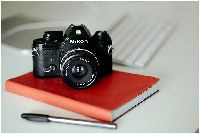 a Nikon camera resting on a red notebook