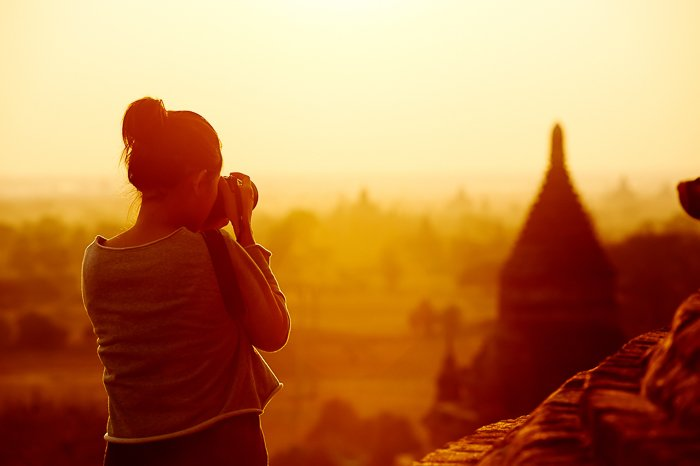 dreamy portrait of a woman taking architecture photographer at sunset