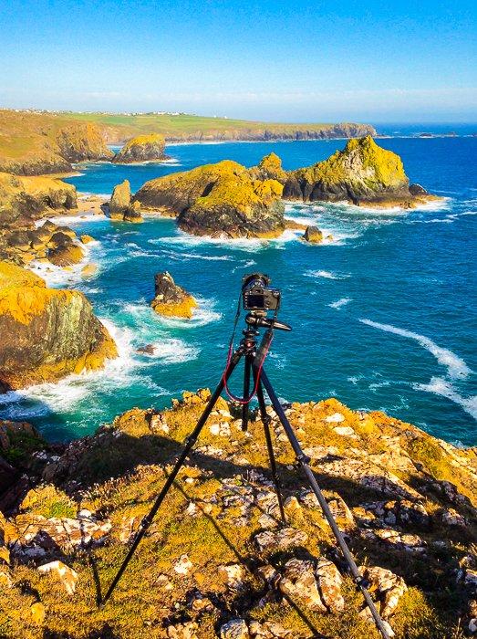a tripod and dslr set up by a stunning coastal landscape
