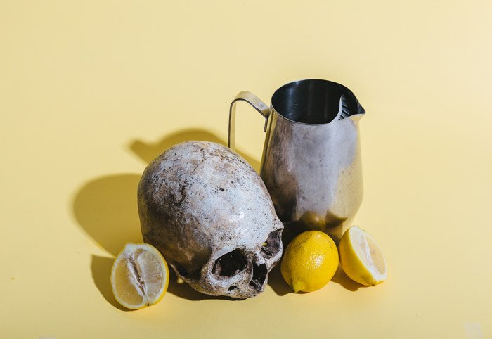 a still life featuring a skull, lemons and a vase on a pale yellow background - symbolism in photography