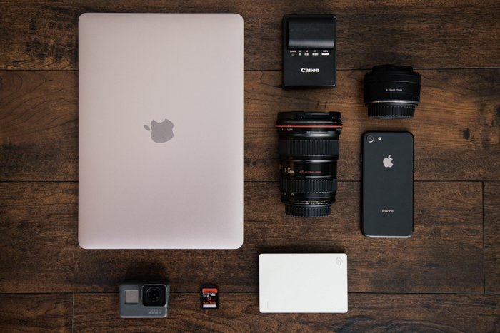 a flat lay of a laptop and camera gear including camera batteries