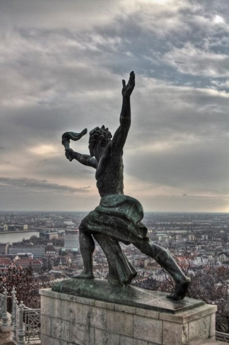 a statue looking over an impressive cityscape in Budapest, Hungary