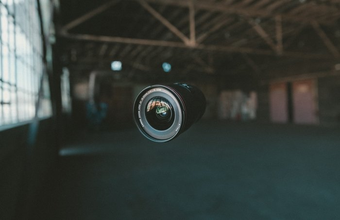 a camera lens suspended mid air, focused on the Canon lens abbreviations