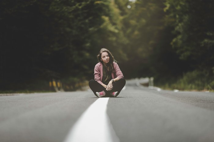 Girl sitting cross-legged in the middle of a countryside road