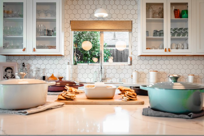 A modern white kitchen with dishes in foreground