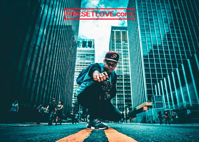 Photo of a man in the middle of the road between skyscrapers urban cool preset