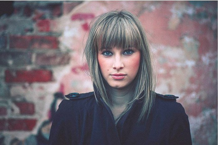 Portrait of a girl in front of a brick wall grainy matte portrait preset