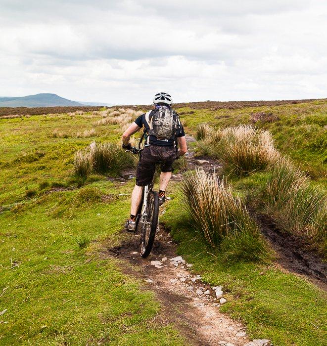 A freeze motion photography shot of a cyclist biking through a countryside path
