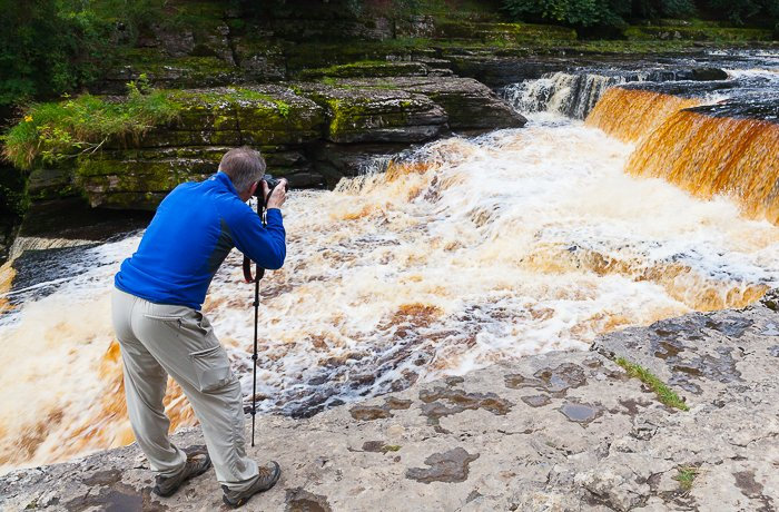 a photographer attempting a freeze motion photography shot of a waterfall