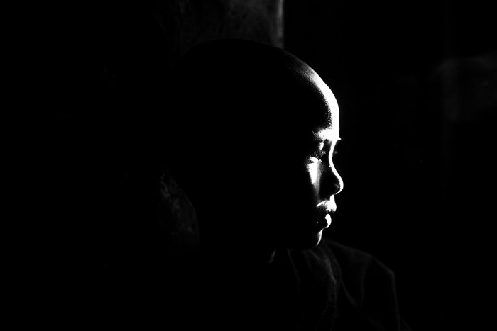 Atmospheric portrait of a monk using reflected light falling on the face