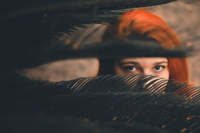 A red haired woman peeping out through leaves