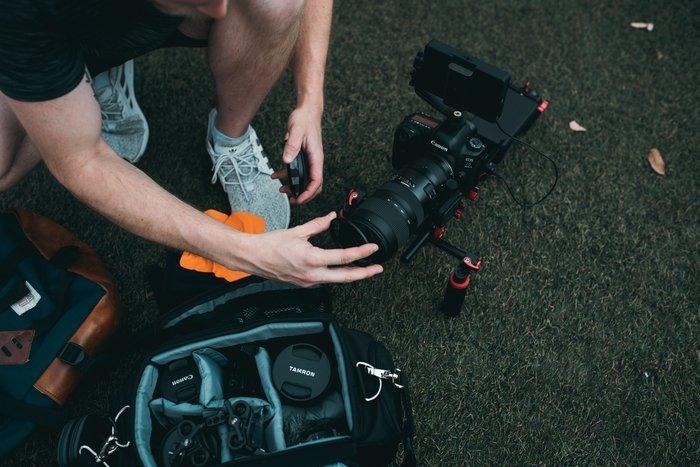 a photographer setting up a Canon dSLR camera with a Tamron lens