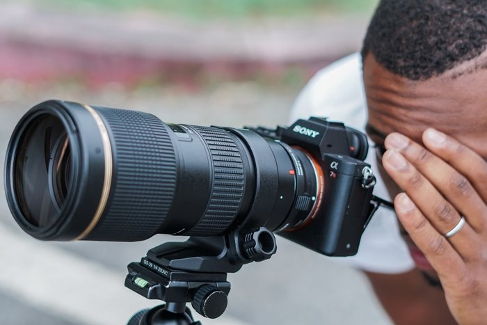 a photographer looking through a Sony dSLR with a Tamron lens