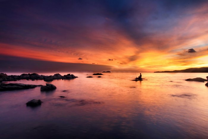 Photo of a waterscape with a fisherman at sunset in purple, orange, and yellow colours