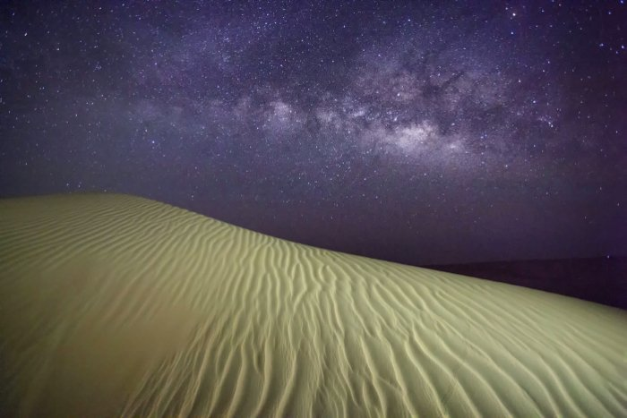 Astrophotography shot of a desert and the night sky above with stars and the milkyway