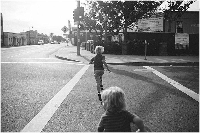 Black and white photo of children running on the street