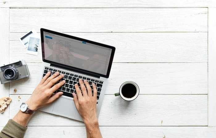 Photo of the hands of a man typing on a laptop with a mug of coffee next to it