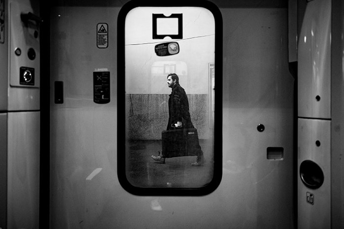 Photo of a man walking with a suitcase reflecting in a mirror